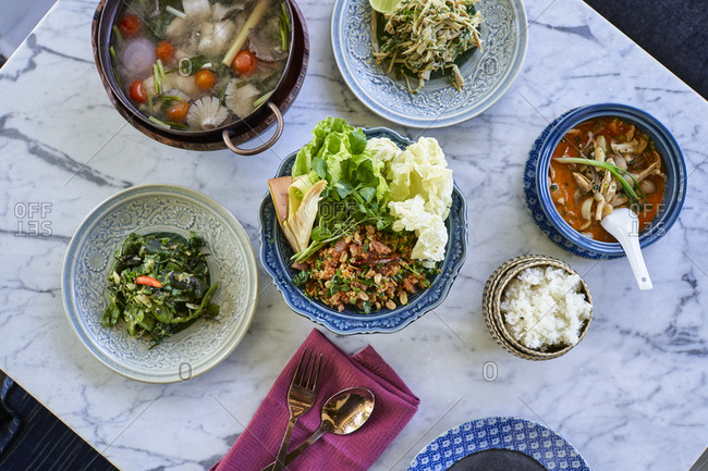 A top down view of several traditional Lao dishes on a marble hotel restaurant table in Luang Prabang, Laos