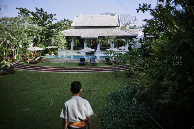 Luang Prabang, Laos - December 19, 2020: Rear view of a staff member walks across the main ground at the Rosewood Hotel