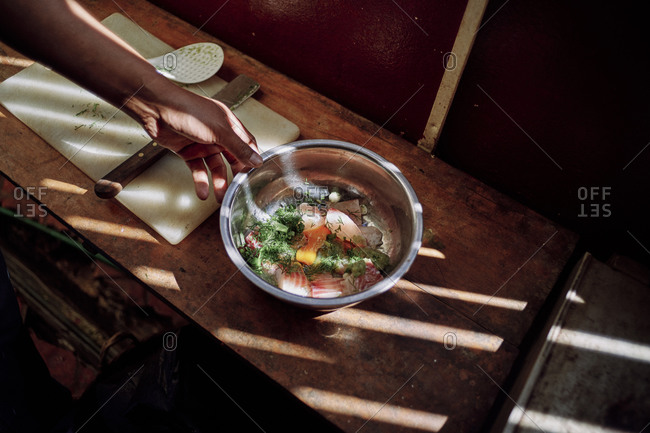 A chef makes a traditional Lao dish of fish and herbs which will then be wrapped into a banana leaf for steaming, in Luang Prabang