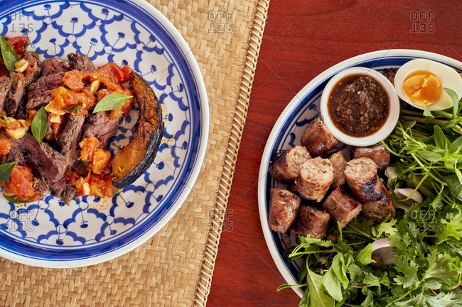Lao-inspired dishes, beef with squash and basil, and traditional Lao sausages with chili dip at a hotel restaurant in Luang Prabang, Laos