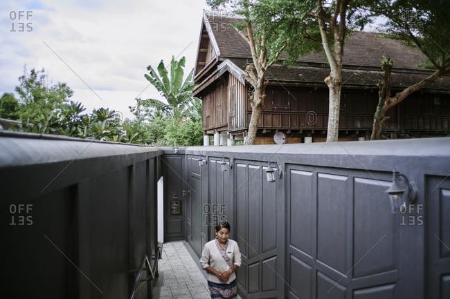 Luang Prabang, Laos - December 19, 2020: A staff member walks through the grounds of the Sofitel Hotel