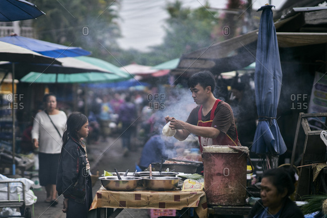Luang Prabang, Laos - December 19, 2020: Man selling food from his street stall to a child at the morning market