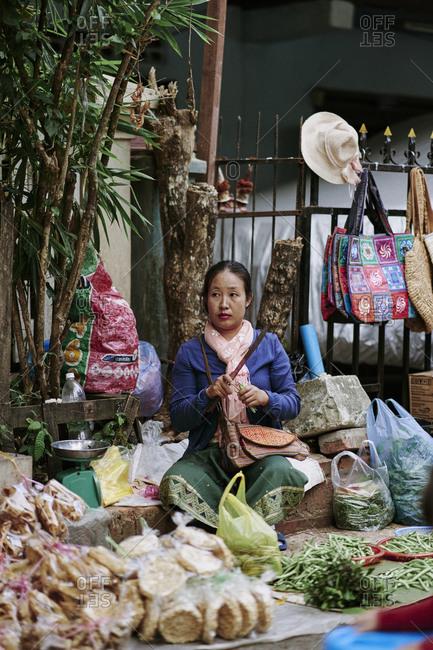 Luang Prabang, Laos - December 19, 2020: Female selling vegetable at her stall at the morning market