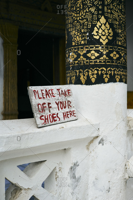A sign at a temple in Luang Prabang, Laos, asking visitors to remove their shoes