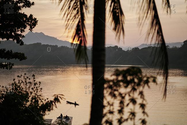 A single boat drifts along the Mekong River at sunset in Luang Prabang, Laos