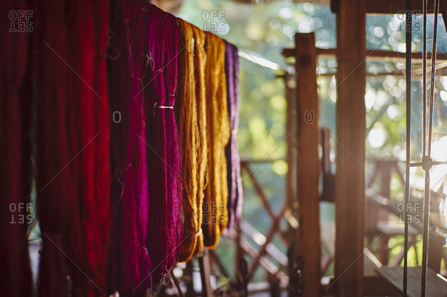 Colorful silks and a traditional loom for weaving scarves and blankets at Mekong Villas in Luang Prabang, Laos