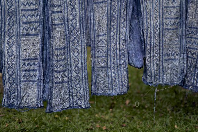 Indigo-dyed fabrics with traditional batik patterns hang to dry outside at Mekong Villas in Luang Prabang, Laos