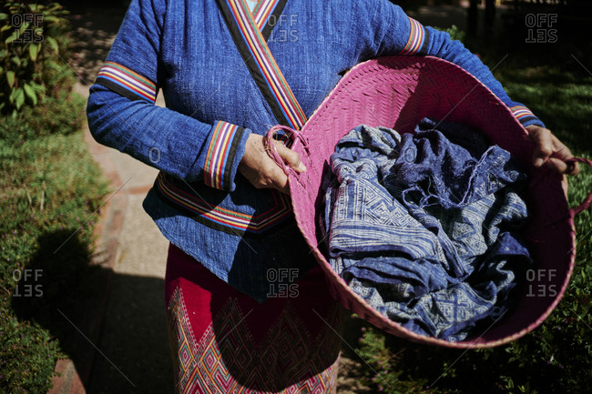 A woman carries indigo-dyed scarves with batik patterns in a basket at Mekong Villas in Luang Prabang, Laos