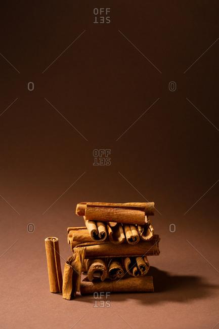 Still life with cinnamon sticks arranged on brown background