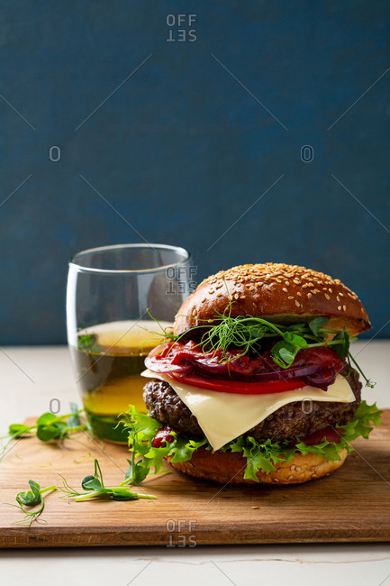 Close up of hamburger on wooden board in front of dark background
