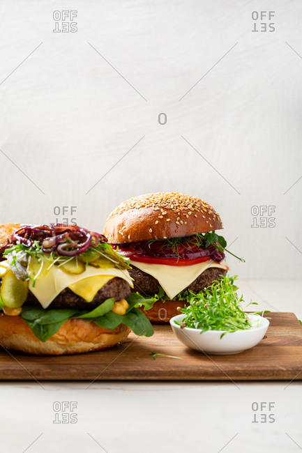 Two tasty American burgers on light surface