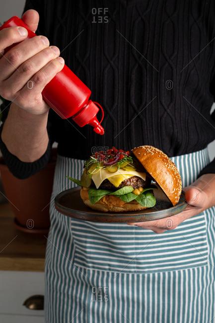 Chef making a fresh and tasty hamburger topped with ketchup