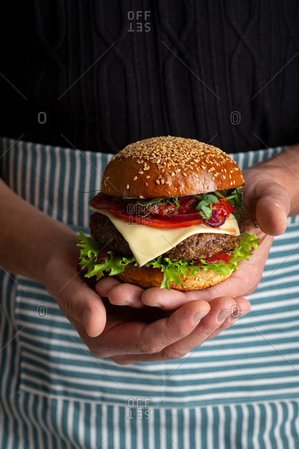 Close up of a fresh and tasty hamburger in chefs hands