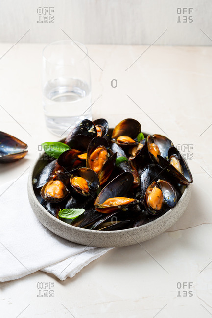 Close up of mussels in deep bowl on white table