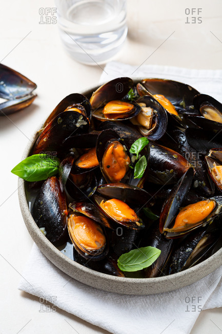 Close up of mussels with garlic sauce and basil