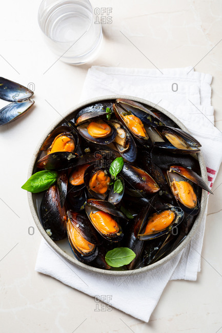 Overhead view of mussels with garlic sauce and basil in a bowl