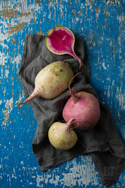 Overhead view of winter radish on rustic blue background and gray cloth