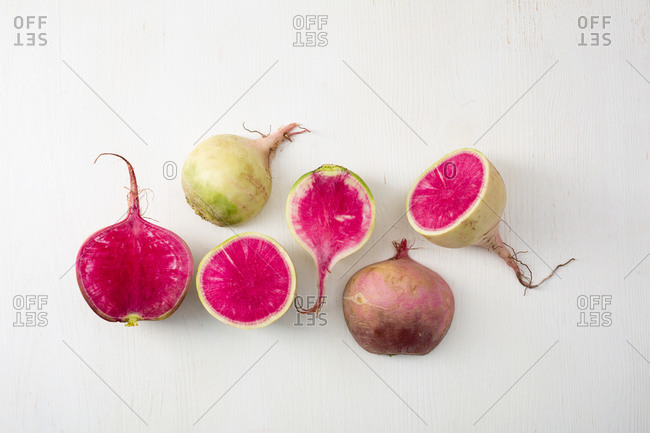 Overhead view of whole and sliced radishes on white surface
