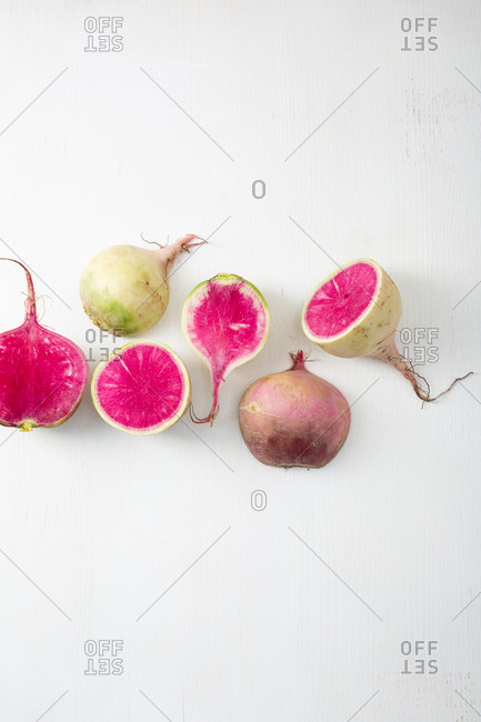 Top view of whole and sliced radishes on white surface