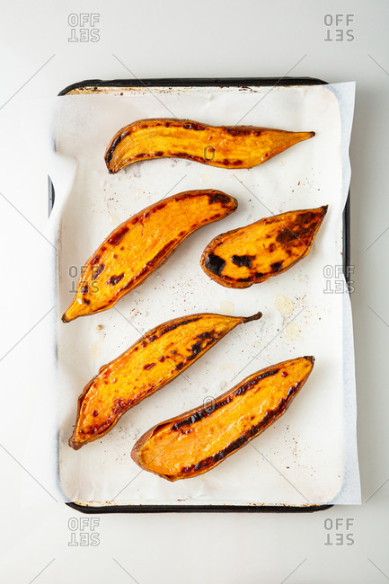 Top view of oven baked sweet potatoes on a tray on white background