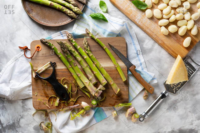 Green asparagus and peeler on cutting board by cheese and gnocchi