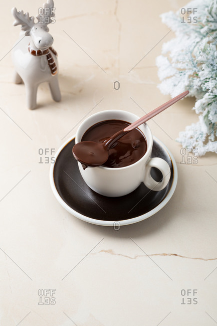 Creamy chocolate dessert in small cup by small decorative moose