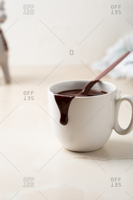 Creamy chocolate pudding dessert in small cup with drip on side