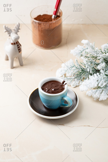 Elevated view of hot creamy chocolate pudding in blue mug by decorative little moose