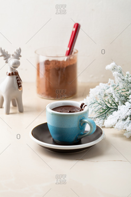 Hot creamy chocolate pudding in blue mug by decorative little moose