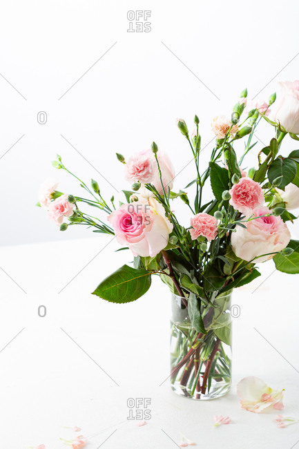Pink roses and carnation flowers in glass vase