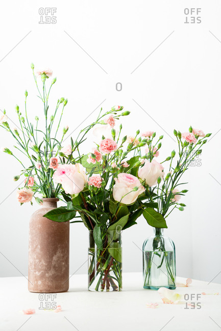 Pink and white floral arrangements on table on light surface