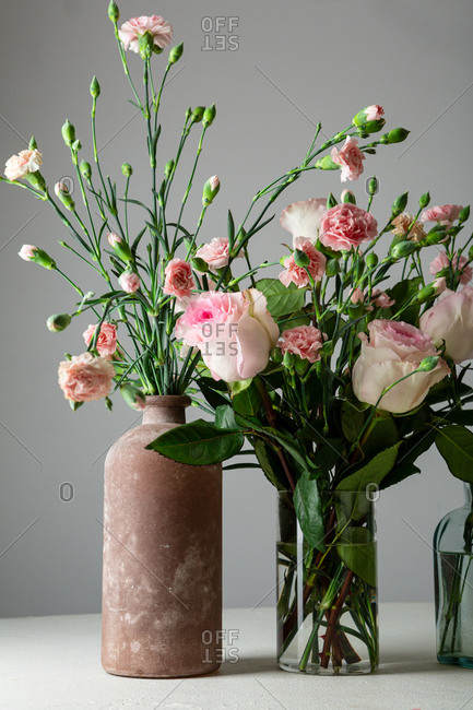 Pink and white flowers bouquets against gray wall