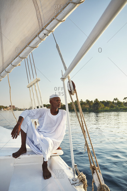 July 12, 2019: Nubian boatman sailing felucca on the Nile River, Aswan