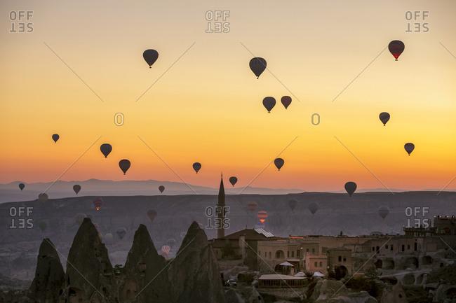 August 13, 2019: Hot air balloons at dawn over Uchisar and Goreme National Park, Cappadocia, Turkey