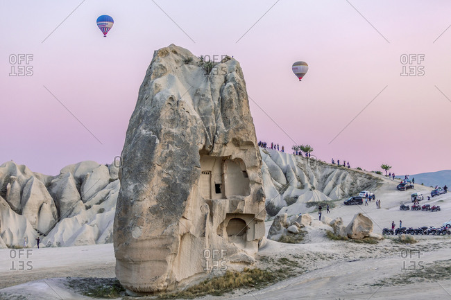 August 14, 2019: Tuff Rock formation with hot air balloons flying high above at dawn, Cappadocia, Turkey