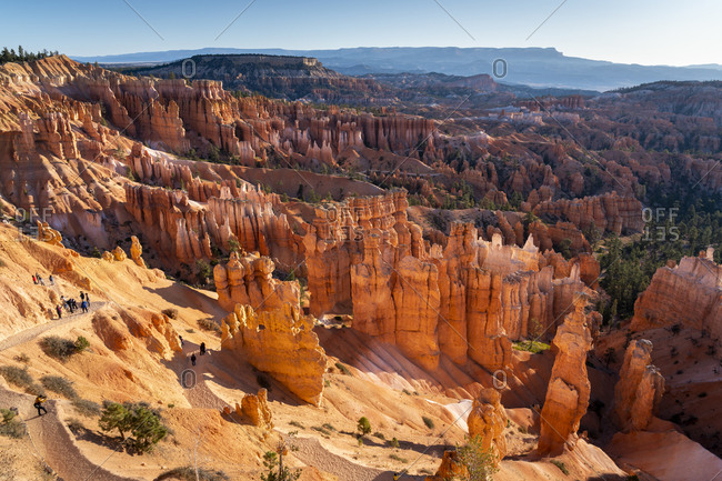 Tourists walking amongst hoodoos in Bryce Canyon amphitheater at Sunset Point after sunrise
