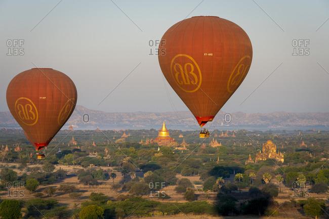 February 12, 2020: Aerial view of hot air balloons trip over pagodas at sunrise, Myanmar, Mandalay