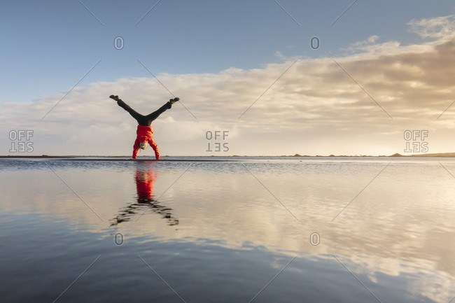 Man doing a cartwheel and his reflection on the water near Vestrahorn mountains in eastern Iceland
