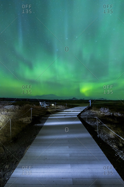 Wooden walkway near Gulfoss waterfall at night with the Northern lights in the dark winter sky