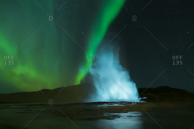 Night shot of Stokkur geyser with the northern lights in the background