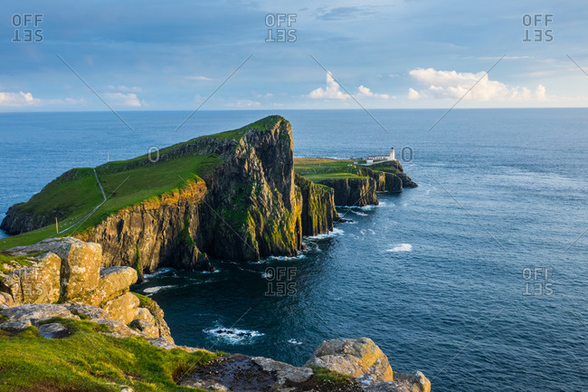 Neist point lighthouse and his the rocky cliffs during a cloudy day at sunset