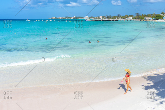 March 6, 2020: Young woman strolls on Miami Beach or Enterprise Beach in Oistins, Barbados
