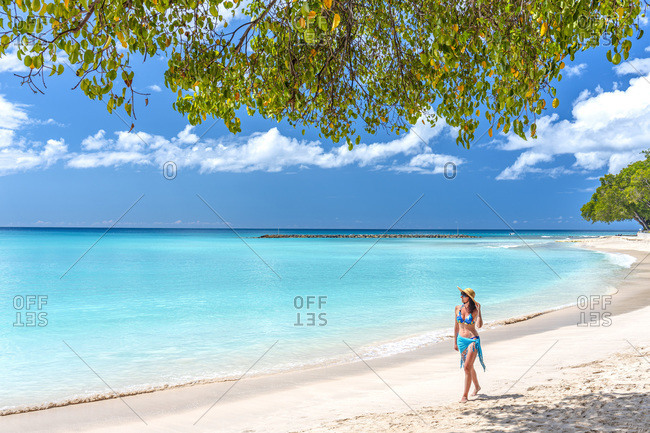 Young woman walking along Sandy Lane beach, the most pristine and prestigious coast of the island of Barbados.