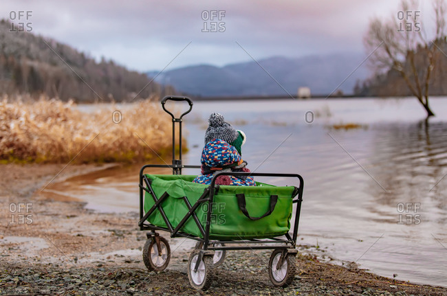 Little kid sitting in a wagon on bank of lake in mountains, poland