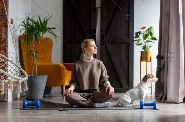 Girl doing meditation on the rug at home next to the dog