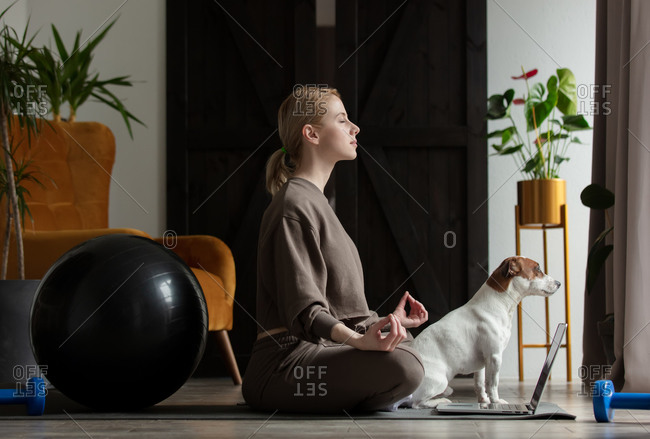 Woman doing yoga exercises at home watching lessons on the internet