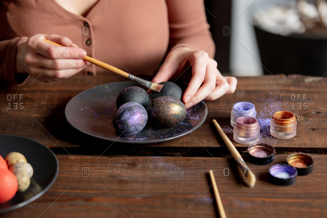 Woman paints easter eggs while sitting at the table at home