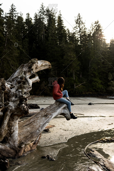 Female sitting on a driftwood piece on the beach in winter clothing