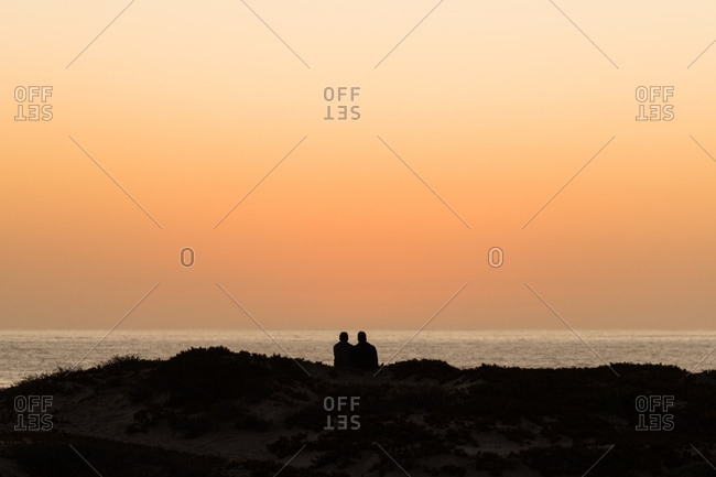 Two people or a couple enjoying the romantic sunset