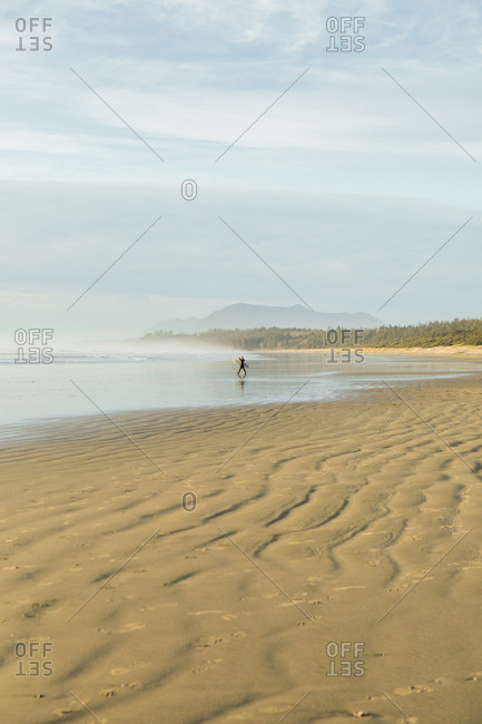 Surfer walking on beach near Tofino BC at sunrise
